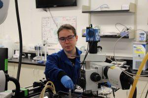 Jelayne, lab technician, working at a microscope